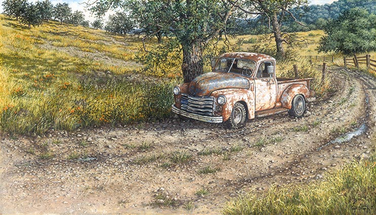 A rusted old truck sits where it was abandoned, along a dirt road next to a gnarled old tree. Recent rains have left thin little puddles along the wheel tracks in the road. Bright yellow wildflowers bloom in the fields surrounding the truck.