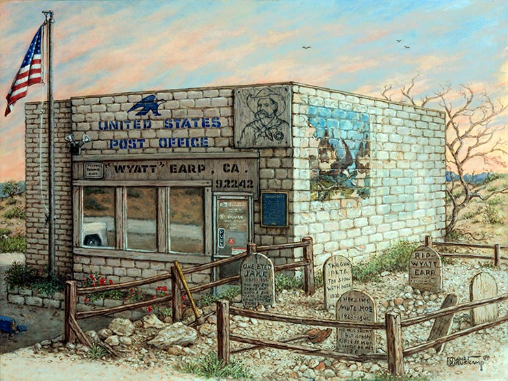The squat block building of the Post Office in Earp, California, sits in front of the beginning of a sunset, the light blue sky painted with wispy orange clouds. A Boot Hill style graveyard next to the building is fenced off by a split rail fence on the rocky ground. The front window reflect the parking lot and the front of a white truck. The side wall of the post office has a fading outdoor mural in the upper left corner. A drawing of Wyatt Earp is attached to the front of the building next to the official blue sign with the eagle USPS logo. Small scrub bushes dot the landscape around the building.